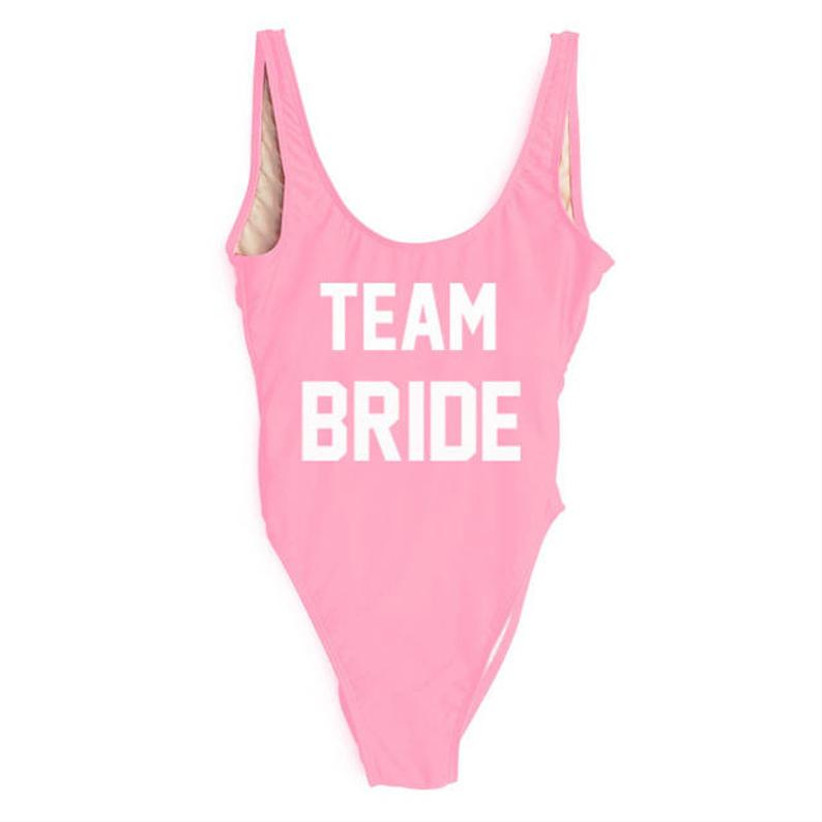 pink one-piece bathing suit with white block text that says