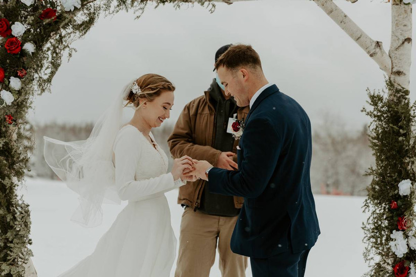 bride and groom exchanging rings during outdoor winter wedding ceremony