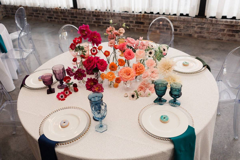 rainbow wedding theme centerpiece with ombre flowers in pink, orange, yellow, and red colors