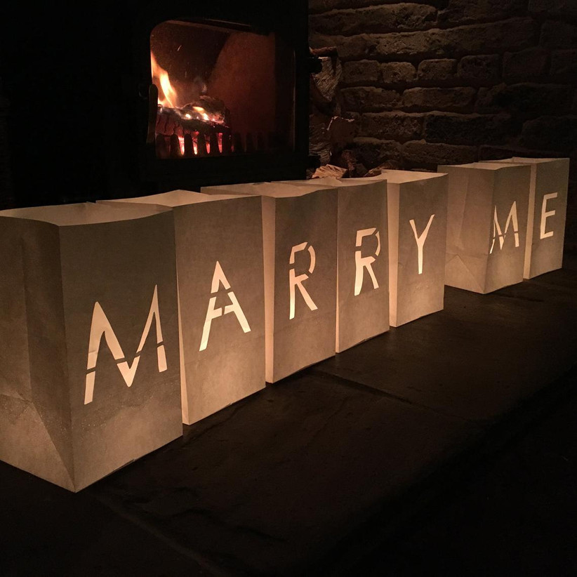 Marry Me candle luminaries in front of a cozy fireplace