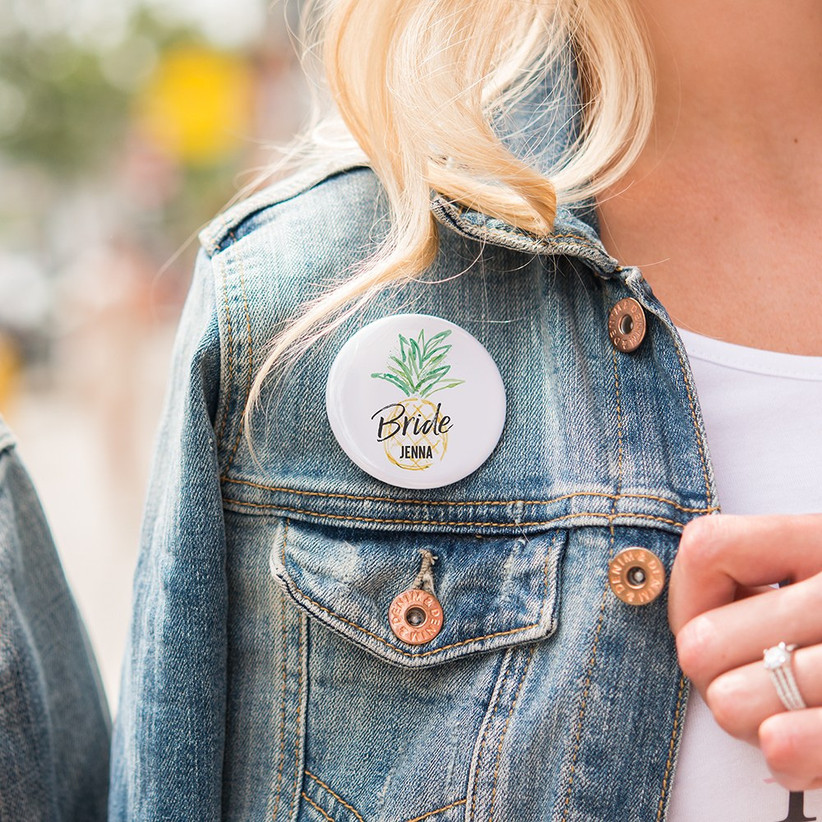 Close up of personalized pineapple motif pin on woman's denim jacket