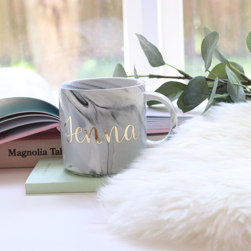 Gray marble-style mug on desk with Jenna in gold lettering