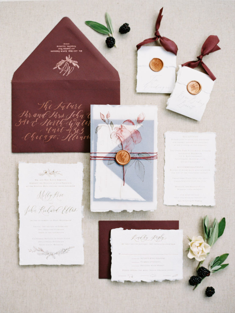 burgundy wedding flat lay with elegant invitations and white flowers