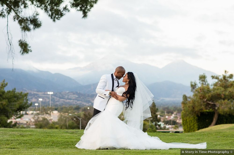 Black couple poses in formal attire outside at wedding venue with hills and mountain views in the background