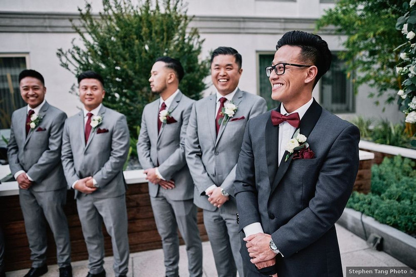 groom wears a dark gray tuxedo with burgundy pocket square. his groomsmen stand slightly out of focus in the background and are wearing light gray suits with burgundy neckties