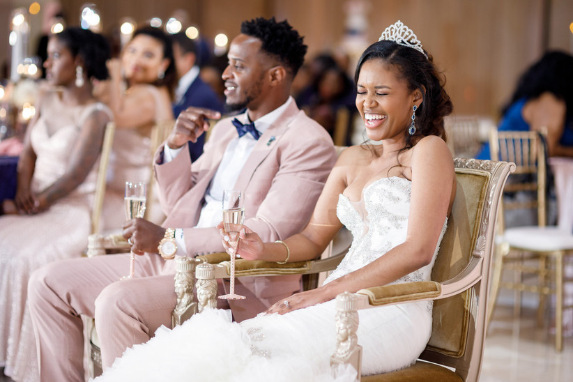 bride and groom, a black couple, laugh while listening to wedding speech during their reception
