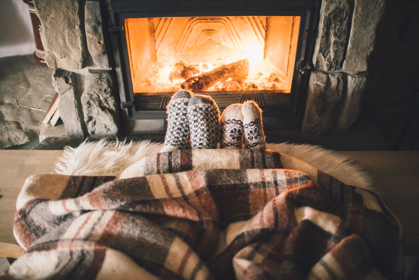 Couple's feet in cozy socks emerging from plaid blanket in front of the fire