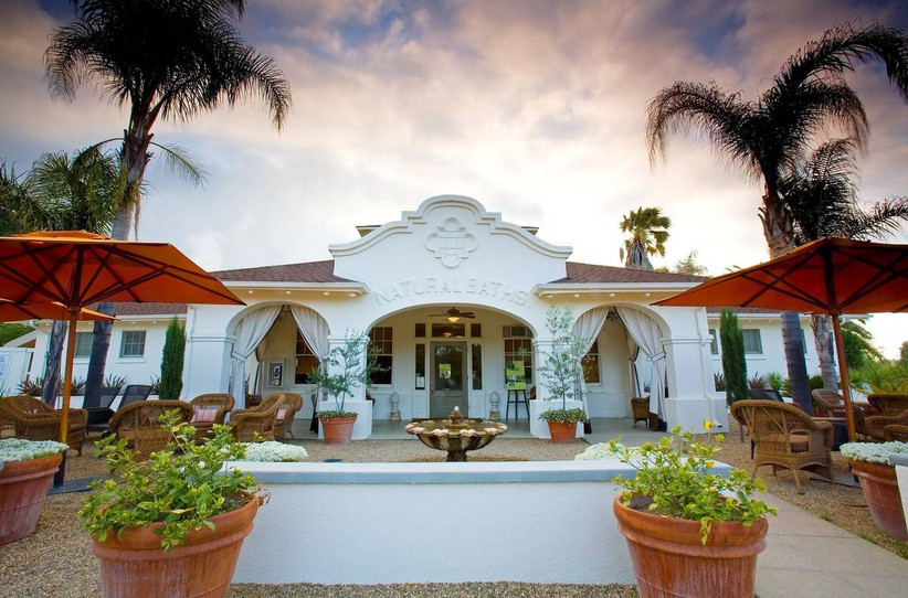 napa wedding venue white Spanish-style building with gravel courtyard and patio tables with umbrellas scattered around
