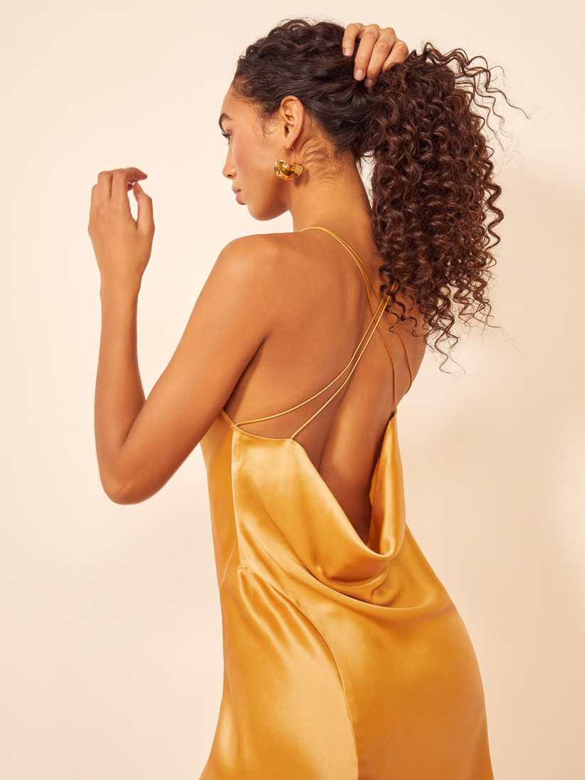 Black model turns her back to the camera while wearing yellow satin bridesmaid dress trend with low cowl-back and criss-cross straps