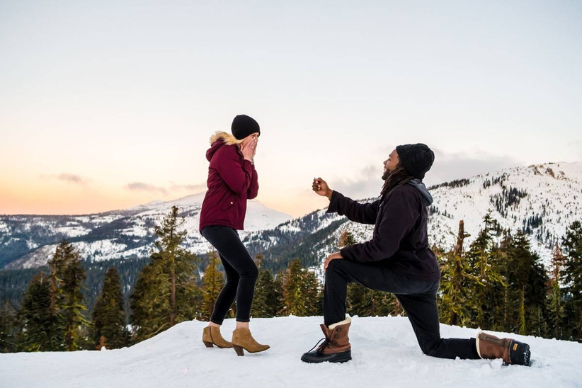 couple proposing on top of a snow-covered mountain