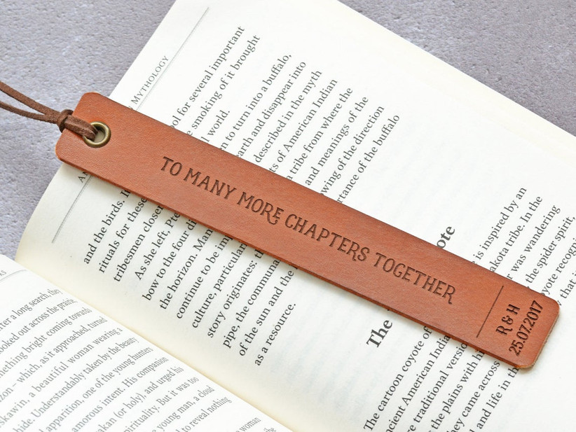 To Many More Chapters Together leather bookmark pictured on the page of an open book
