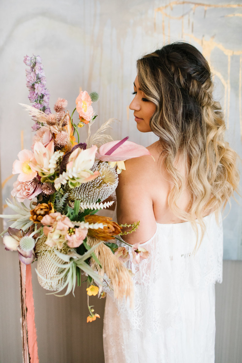 bride holds boho beach wedding bouquet including anthurium, banksia flower, and air plants