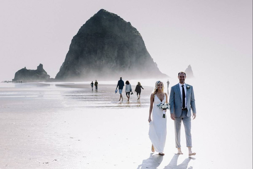 bride and groom walk on cannon beach with haystack rock in the background