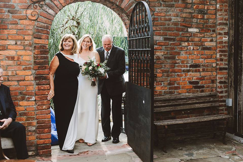 bride flanked by parents walking down the aisle