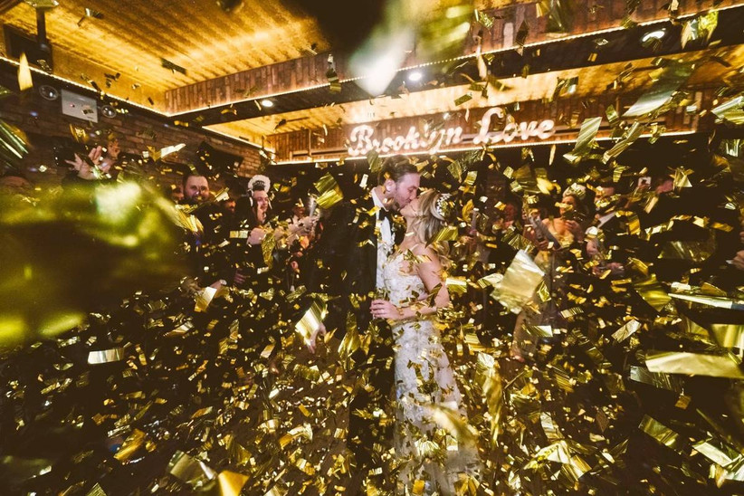 bride and groom kiss on the dance floor while gold confetti falls from the ceiling