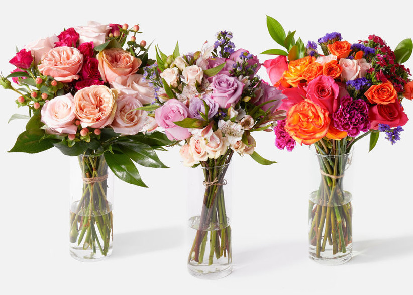 Three beautiful Urban Stems bouquets in glass vases