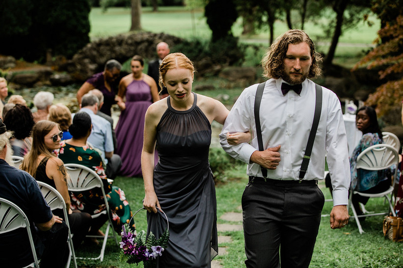 Bridesmaid and groomsman walking together with guests in their seats wearing fall wedding atitire