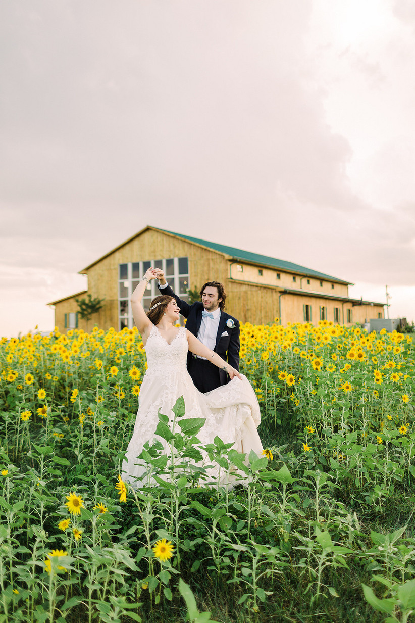 groom twirls bride in a field of sunflowers with barn wedding venue behind them in the distance