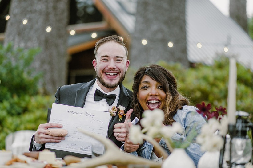 Interracial couple smiles and celebrates while holding their marriage certificate after covid wedding