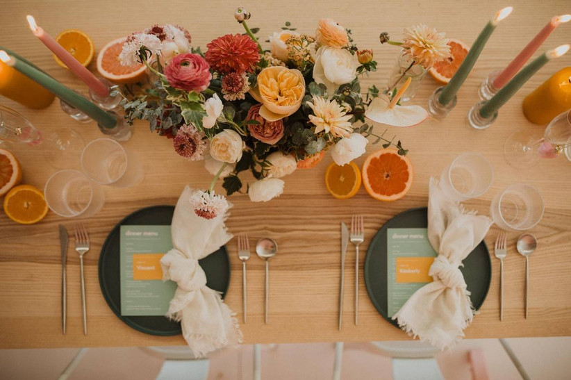 photo of wedding tablescape from above light wooden table with colorful pink, yellow, and orange flower centerpiece with tall colorful taper candles on both sides and fresh orange slices placed throughout the tablescape as decorative detail