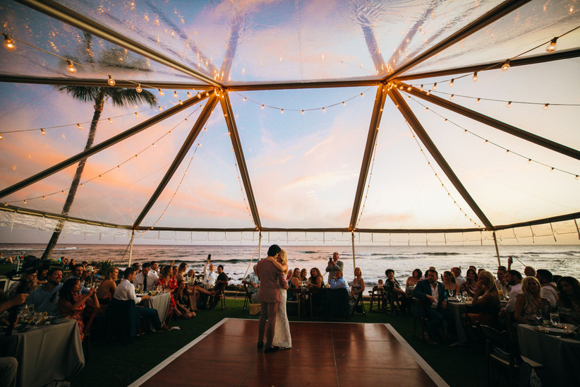 couple shares first dance in the middle of a clear top tent at sunset with ocean view in the background