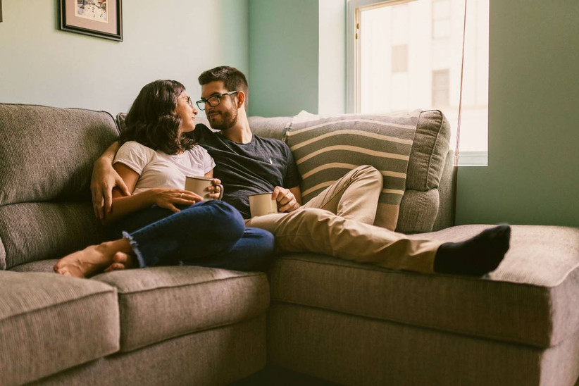engaged couple holding coffee mugs and sitting on couch
