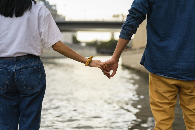 couple holding hands overlooking the seine river