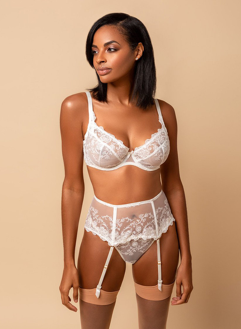 Model wearing sexy bridal lingerie set including white lacy bra, garter belt, and briefs