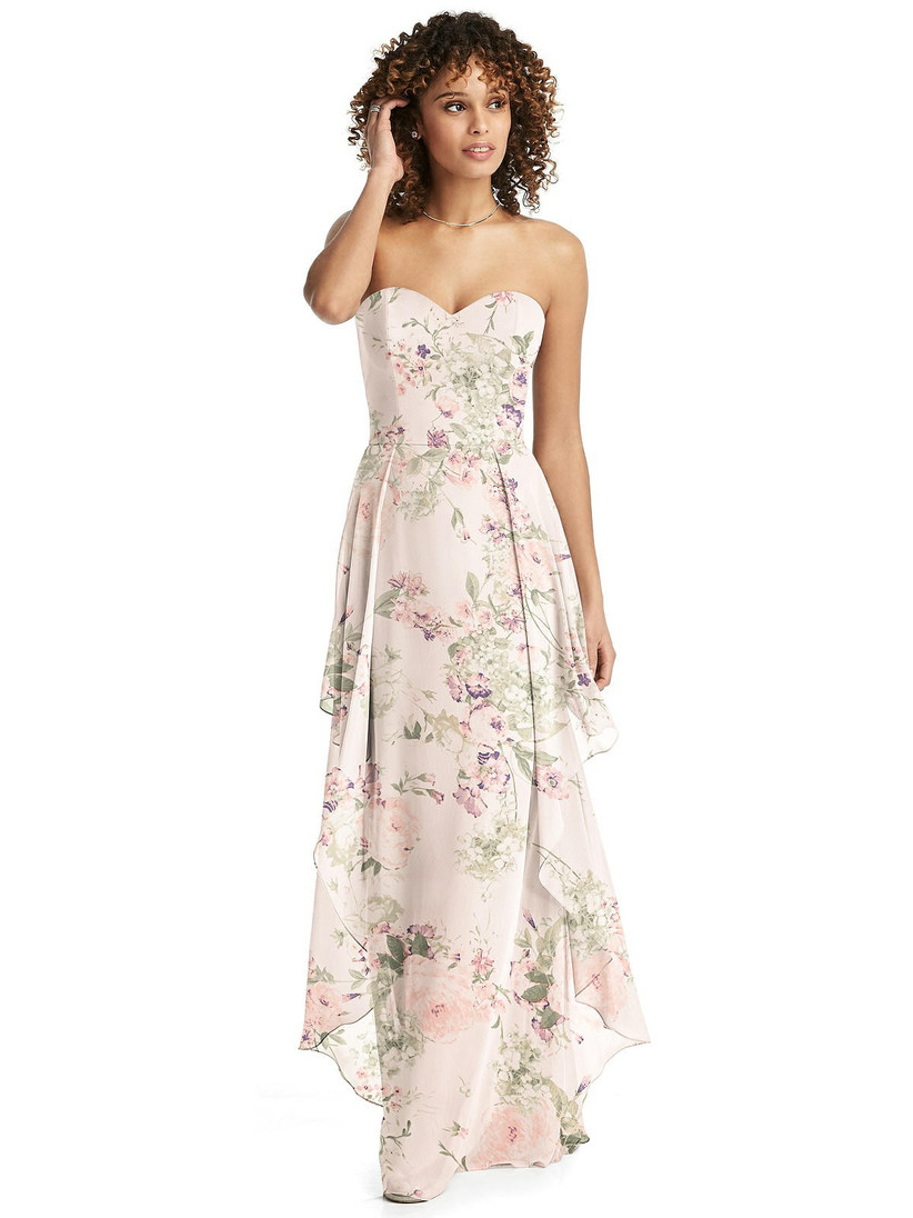 Model wearing light and airy bridesmaid dress with layered skirt and strapless sweetheart neckline in blush pink floral pattern