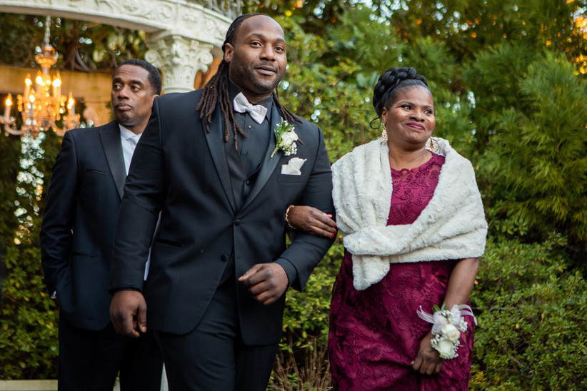 Groom and mother of the groom wearing pink jewel tone dress and faux fur wrap