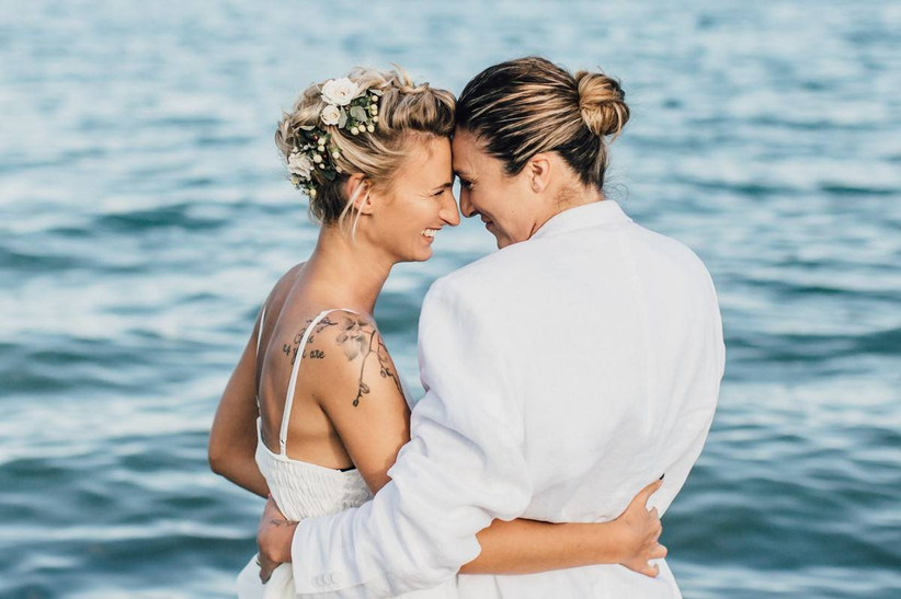 two brides pose on the beach and sweetly look into each other's eyes