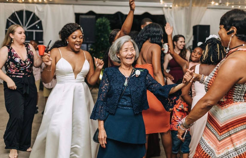 mothers of the bride and groom laugh while dancing together during reception