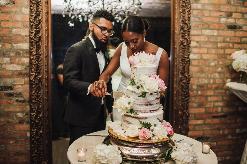 Black bride and groom hold knife together while they cut into a semi-naked wedding cake decorated with white frosting and pink flowers
