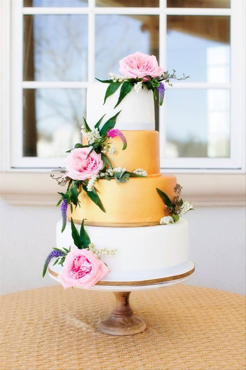 tall wedding cake is displayed on a wooden stand with fresh flowers