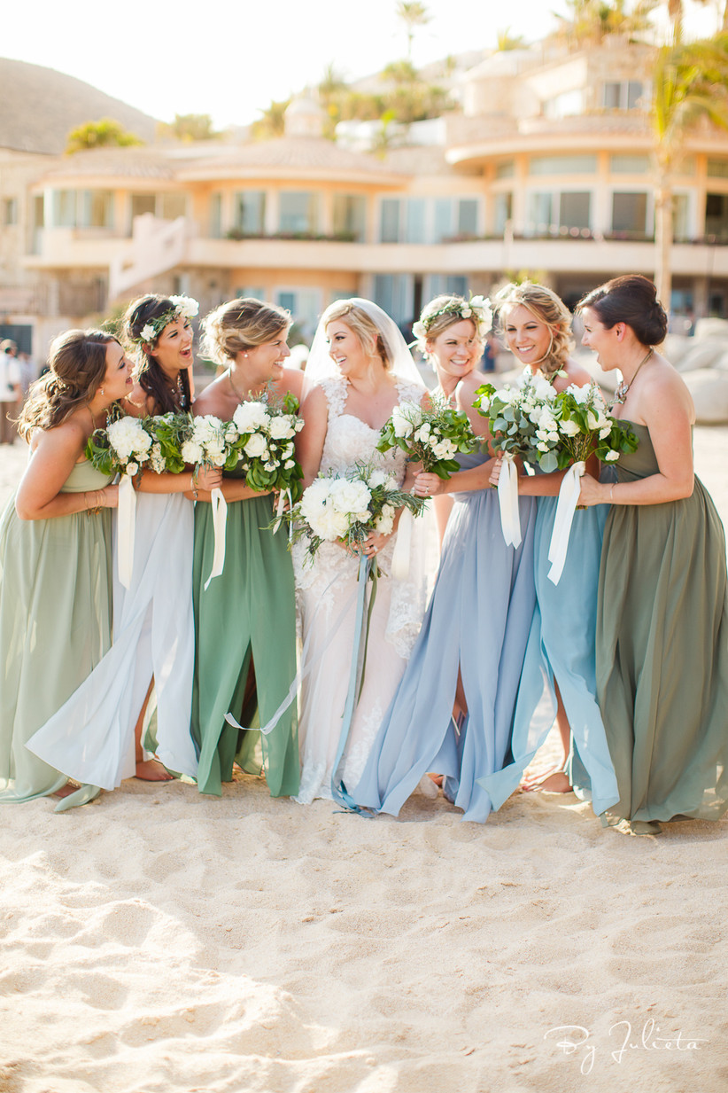 Bridesmaids surrounding bride and wearing pastel hues of green, purple, and blue