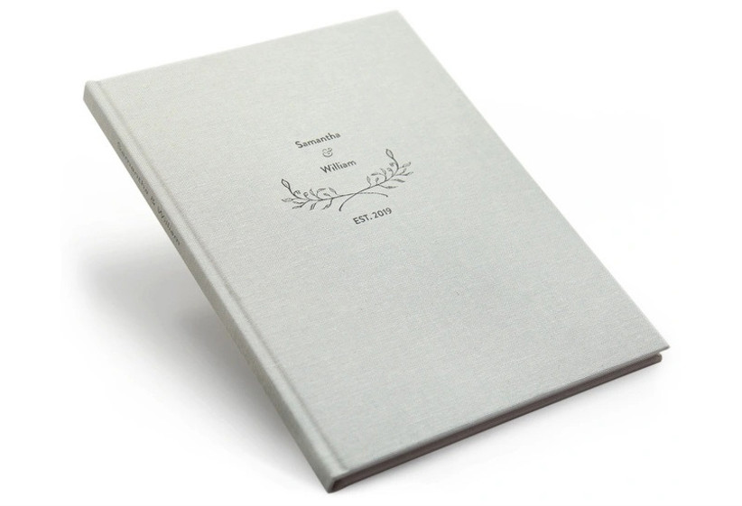 Minimalist light gray linen wedding photo book with couple's names and wedding date on the cover