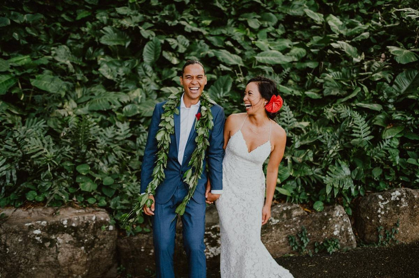 hawaiian bride and groom laugh while holding hands