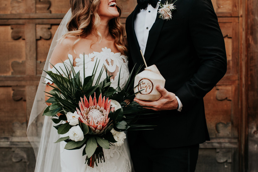 bride holds bouquet with pink king protea while groom stands next to her holding coconut shell cup
