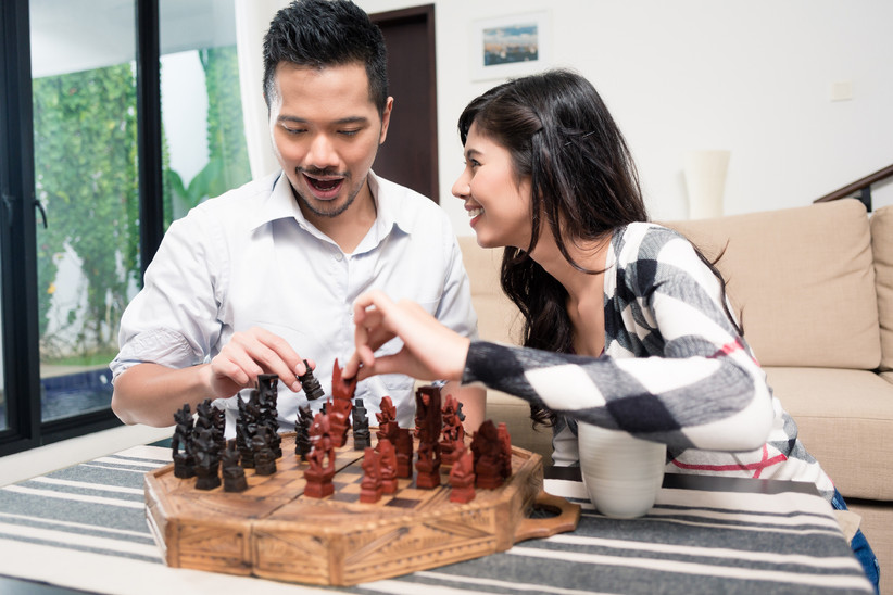 Happy couple smiling and playing chess at home together
