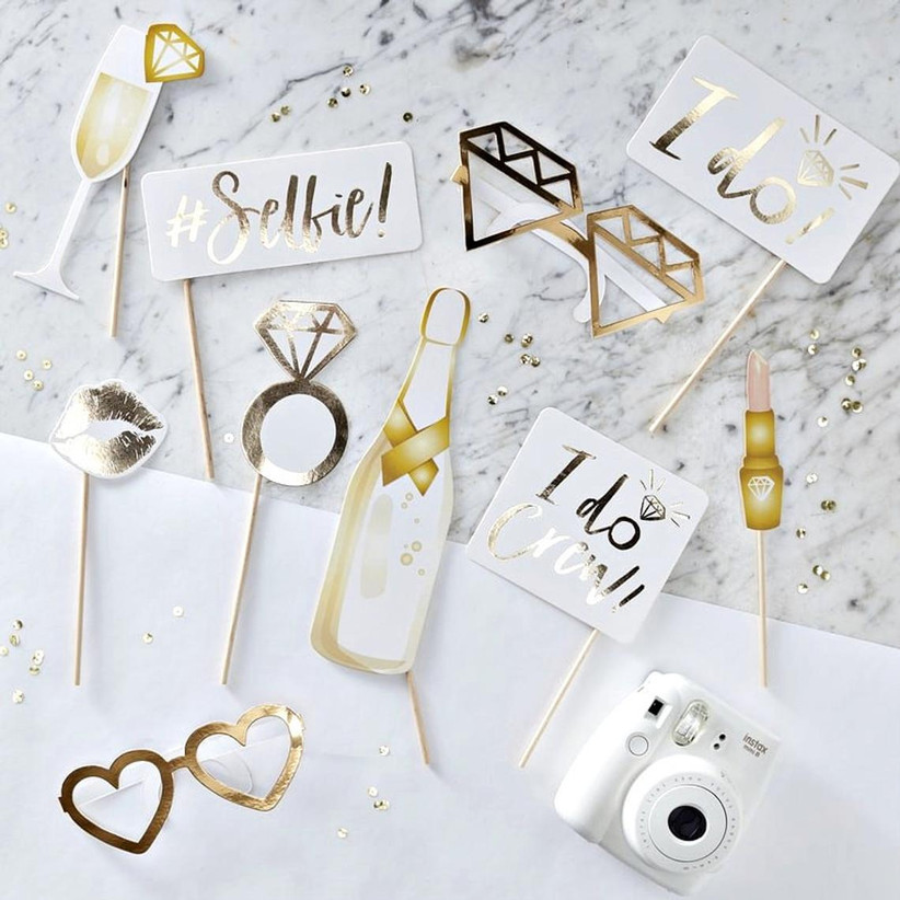 Spread of bachelorette party photo props with white and gold design