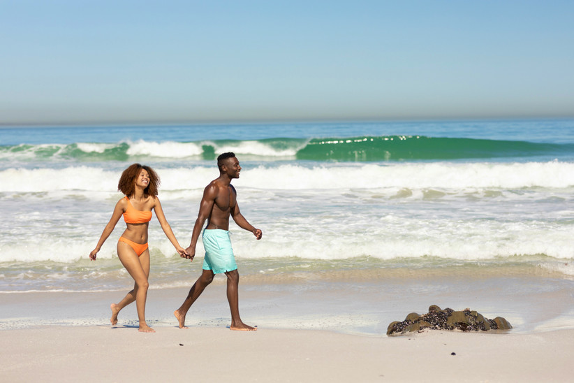 couple holding hands walks along the beach with waves crashing behind them
