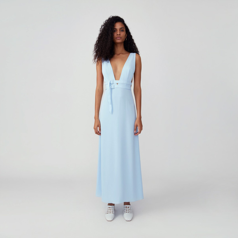 Model wearing deep V cut-out pastel blue bridesmaid dress with buckles