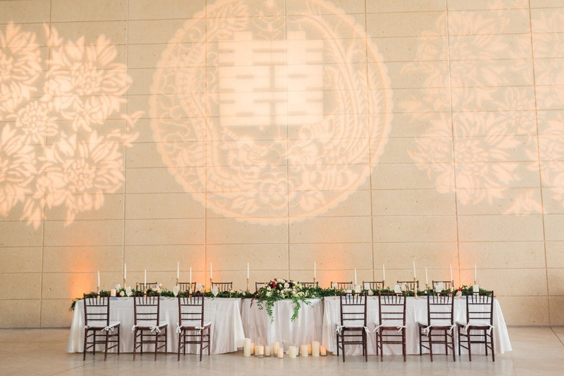 long wedding banquet table with dark brown chairs against a large blank wall with chinese symbol projection