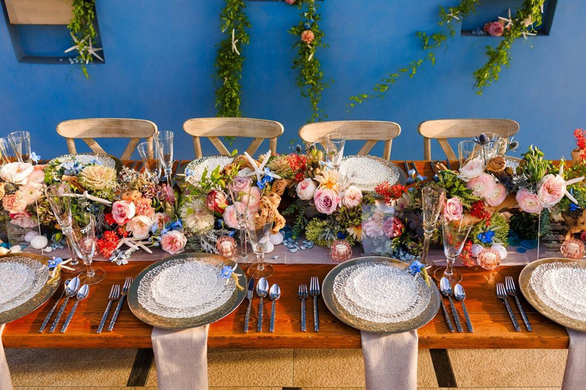 long reception banquet table with colorful pink blue and green flower centerpiece accented with starfish and votive candles