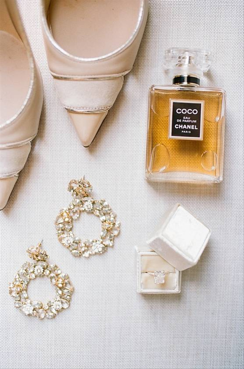 wedding flat lay with high heels, earrings, ring box and coco chanel perfume bottle