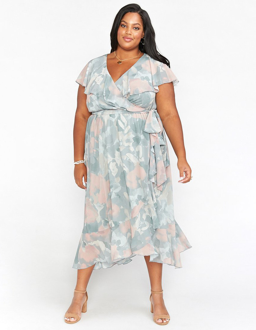 Plus-size model wearing midi-length ruffled pastel dress with abstract floral pattern