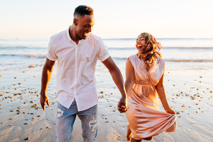 black couple laughs while looking at each other and holding hands walking on a beach at sunset
