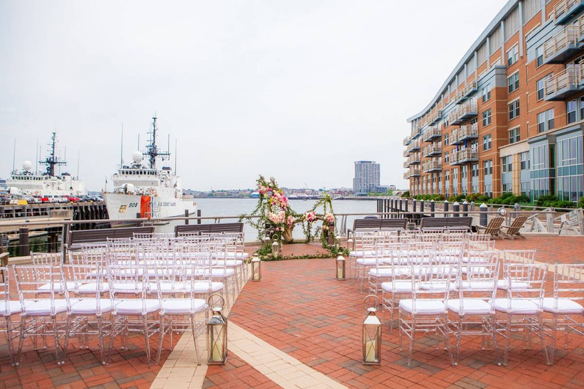 waterfront boston wedding venue ceremony overlooking boston harbor with ships and skyline in the distance