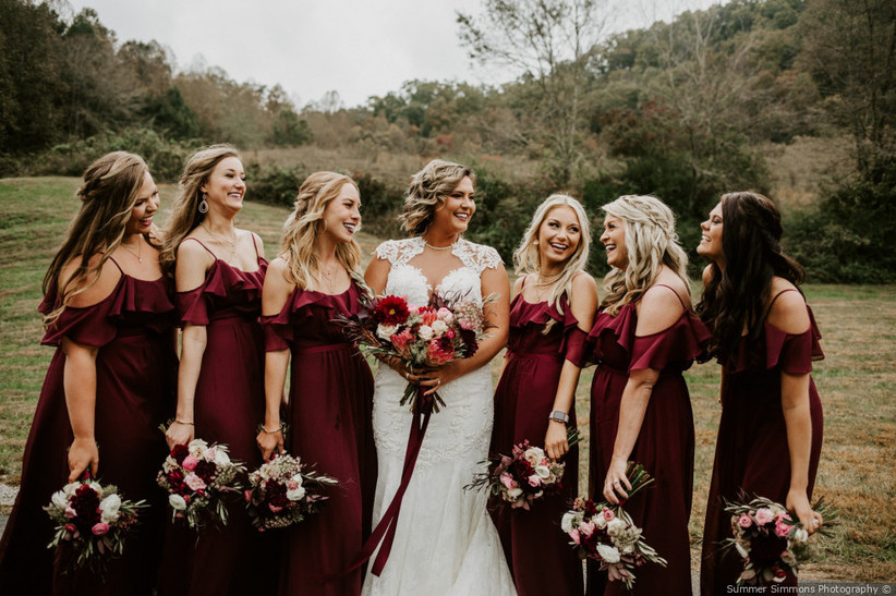 Bride and bridesmaids posing outside with bridesmaids wearing burgundy