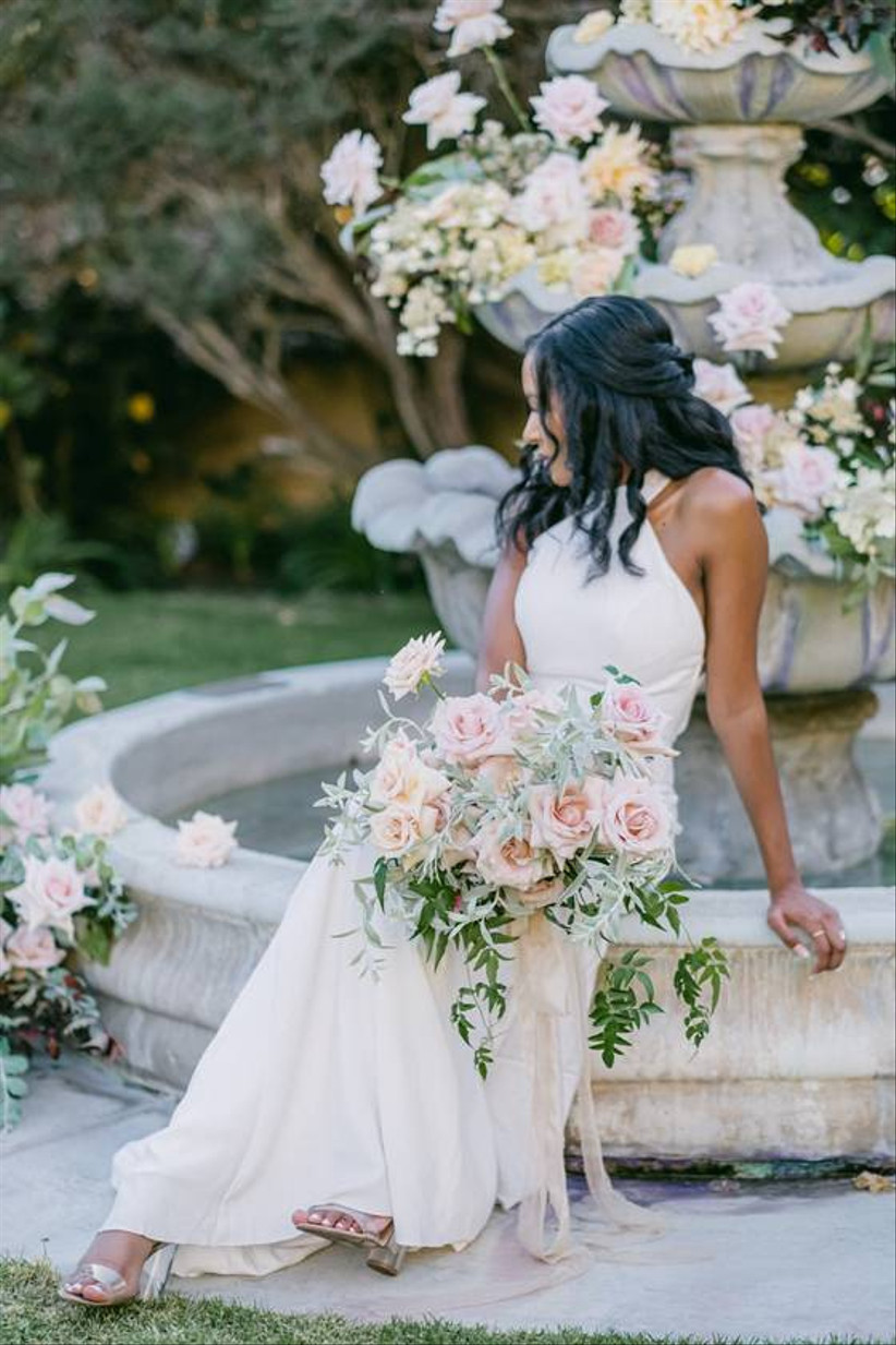 Black bride sits on the edge of a stone fountain holding a blush garden rose bouquet in her lap